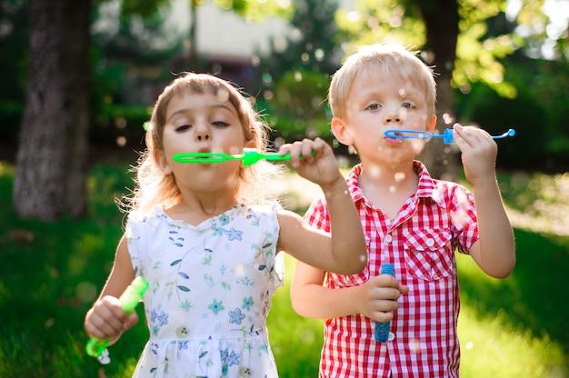 Enfant et amis jouent une bulle dans l'aire de jeu avec coucher de soleil