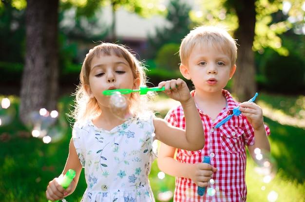 Enfant et amis jouent une bulle dans une aire de jeux avec fond de coucher de soleil, enfant, enfant, école, jeu et fond d'été