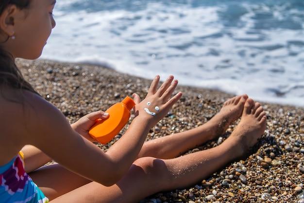L'enfant applique de la crème solaire sur sa main. mise au point sélective. enfant.