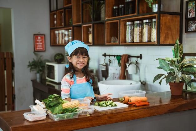 Enfant apprenant à cuisiner à la maison