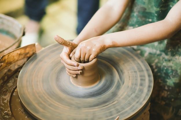 Enfant apprenant à sculpter un pot en argile