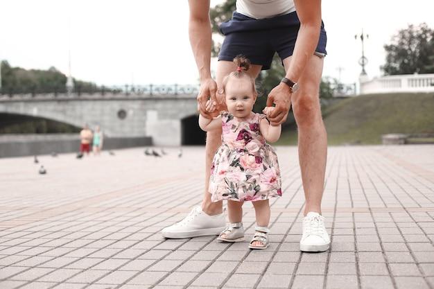 L'enfant apprend à marcher. le père soutient l'enfant et lui apprend à marcher.
