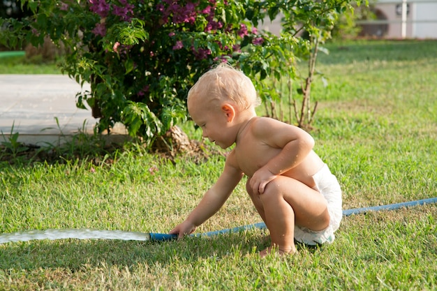 Enfant arrosant l'herbe dans la cour