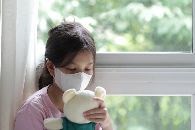 Enfant asiatique de 6 ou 7 ans portant un masque médical.petite fille debout près de la fenêtre et regardant à l'extérieur.elle a l'air triste, s'ennuie.elle peut être malade ou mise en quarantaine à cause de la maladie du coronavirus 19 (covid-19).