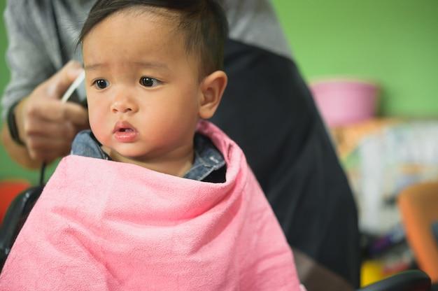 Enfant asiatique en bas âge obtenant sa première coupe de cheveux.