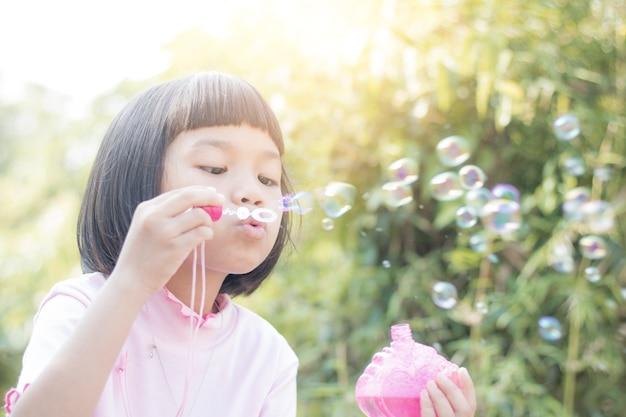 Enfant asiatique drôle, soufflant des bulles dans le parc