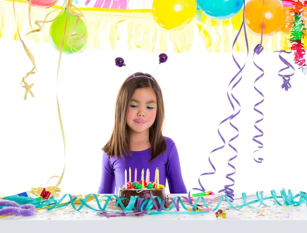 Enfant asiatique enfant fille dans la fête d'anniversaire faim tonge