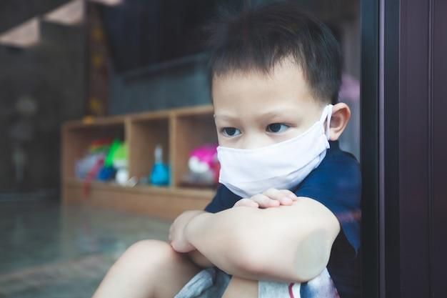 Enfant asiatique garçon portant un masque de protection à l'extérieur par la fenêtre et rester à la maison en quarantaine contre le coronavirus covid-19 et la pollution de l'air pm2.5.