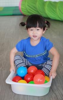 Enfant asiatique jouant des balles colorées dans un plateau en plastique à la chambre d'enfant