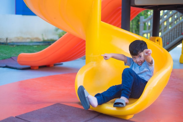 Enfant asiatique, jouer, glisser, à, les, cour de récréation