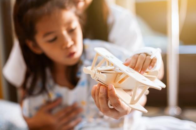 Enfant asiatique malade jouant avec un avion en bois jouet avec sa mère pendant son séjour à l'hôpital