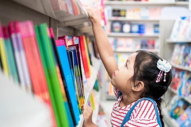 Enfant asiatique mignon fille sélectionnez livre sur étagère en librairie au supermarché