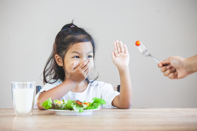 Un enfant asiatique n'aime pas manger de légumes et refuse de manger des légumes sains