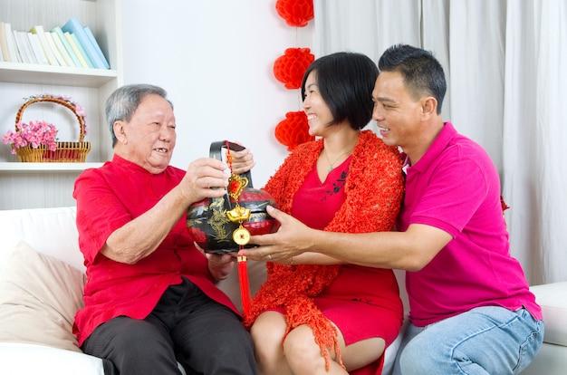 Enfant asiatique présentant un panier-cadeau au parent lors du nouvel an chinois