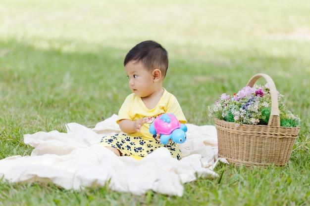 Enfant asiatique souriant, les cheveux et les yeux noirs de l'enfant en bas âge sont assis sur du coton blanc dans l'herbe verte seul et jouent à des jouets.