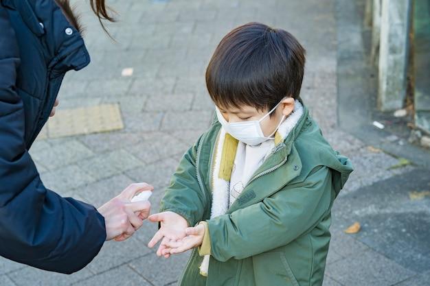 Enfant asiatique stérilisé par pulvérisation sur le pouce à l'extérieur