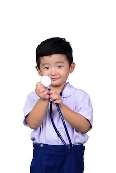 Enfant asiatique en uniforme scolaire jouant un stéthoscope médical avec un tracé de détourage.
