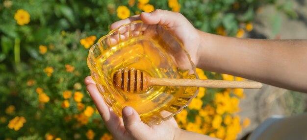 Enfant une assiette de miel dans les mains. mise au point sélective.