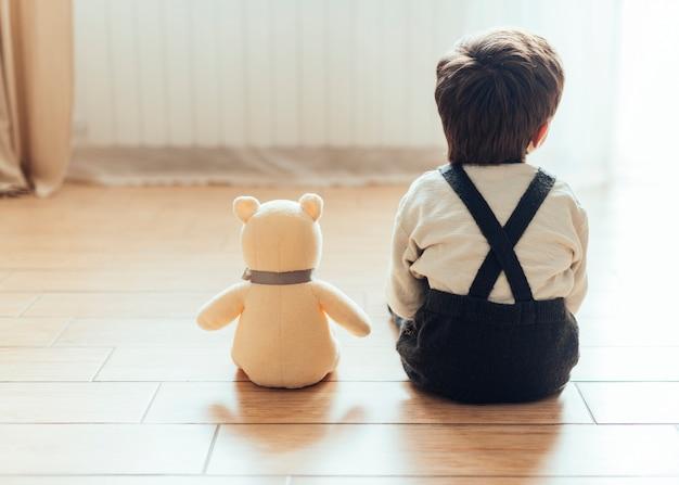 Enfant assis à côté d'un ours en peluche