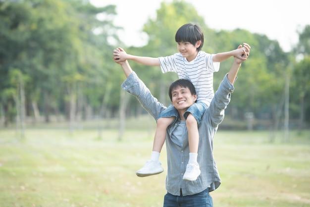 Enfant assis sur les épaules du père dans un parc public