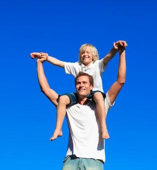 Enfant assis sur les épaules de son père