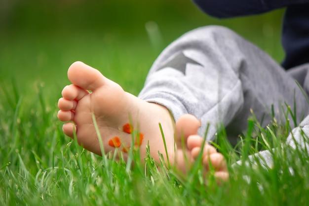 Enfant assis sur l'herbe, souriant sur la jambe de l'enfant avec de la peinture