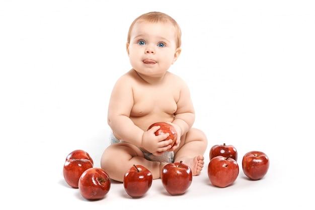 Enfant assis avec des pommes