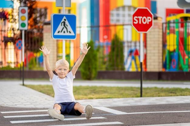 Enfant assis sur la route à un passage pour piétons