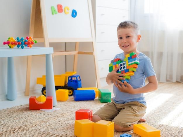 Enfant assis sur le sol dans la salle en jouant