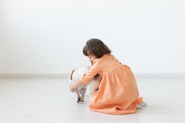 Enfant assis sur le sol avec mignon chiot jack russell terrier