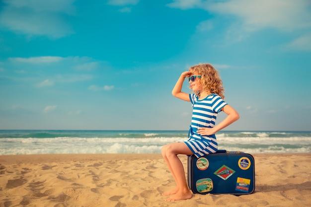 Enfant assis sur une valise à la plage sur fond de mer et de ciel