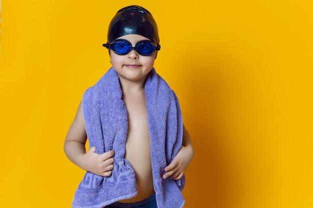 Enfant athlète portant des lunettes de natation bleues et un bonnet en caoutchouc noir et une serviette se dresse sur un mur jaune