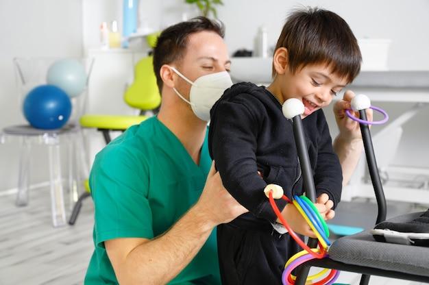 Enfant atteint de paralysie cérébrale en physiothérapie dans un centre de thérapie pour enfants.