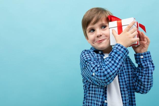 Enfant attrayant détient un cadeau à l'oreille sur un bleu clair