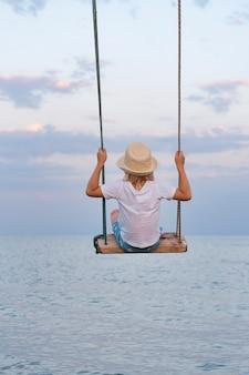 Enfant au chapeau de paille se balançant au-dessus de la mer. cadre vertical.