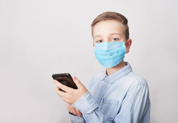 Enfant au masque médical avec téléphone portable. coronavirus et pollution de l'air concept pm2.5. symptômes viraux. concept d'épidémie, de grippe, de protection contre les maladies, de vaccination. la grippe. soins médicaux.