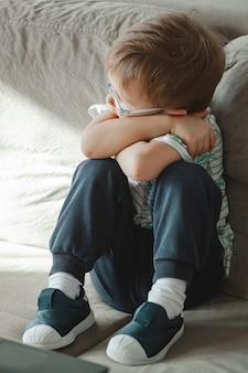 Un enfant autiste à lunettes est assis sur le canapé et triste