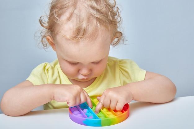 Un enfant aux cheveux bouclés attrape un jouet anti-stress dans le cul. education des enfants à l'aide de jeux populaires.
