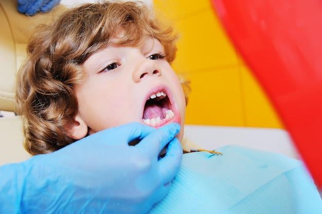 Un enfant aux cheveux bouclés se laisse aller et grimace dans un fauteuil dentaire