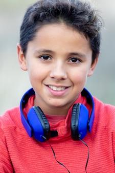 Enfant aux cheveux noirs, écoute de la musique avec des écouteurs bleus