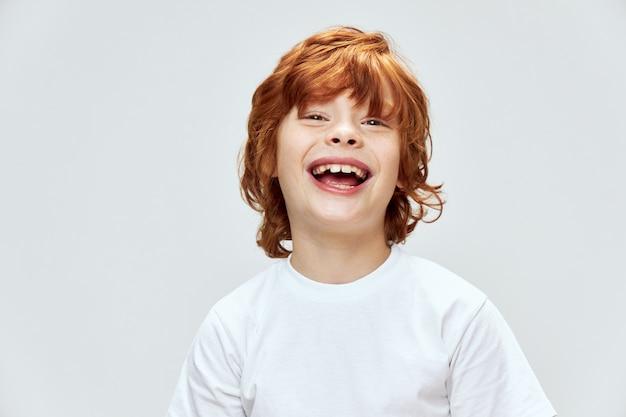 Enfant aux cheveux roux avec grand sourire ouvert en t-shirt blanc