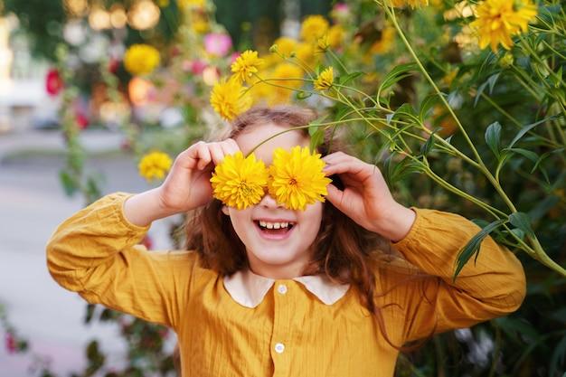 Enfant aux yeux de fleurs montrant les dents blanches, en plein air l'été.