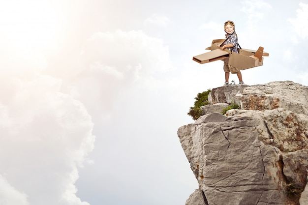 Enfant avec avion en carton sur un rocher