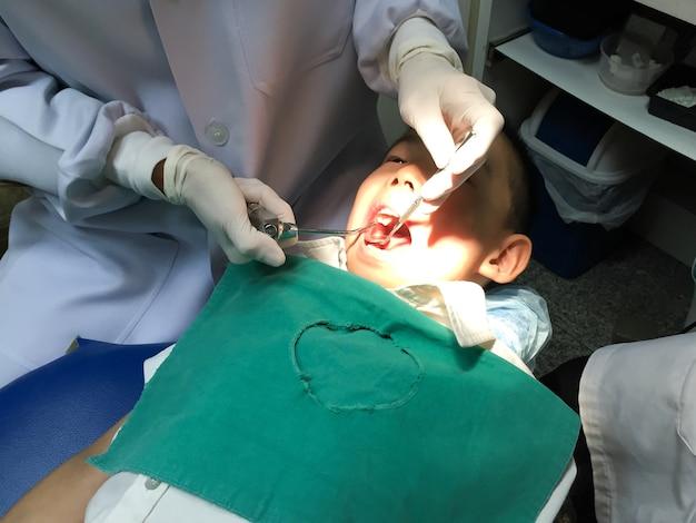 Enfant ayant un examen de la bouche dans une clinique dentaire