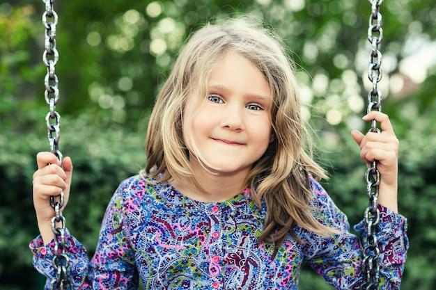 Enfant sur balançoire dans le parc d'été
