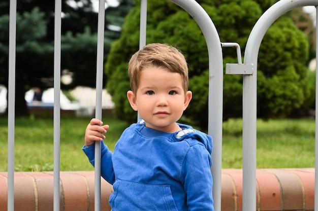 Enfant avec barrières métalliques.