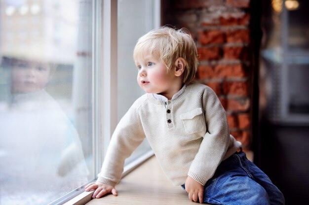 Enfant en bas âge assis sur le rebord de la fenêtre et regardant la fenêtre panoramique