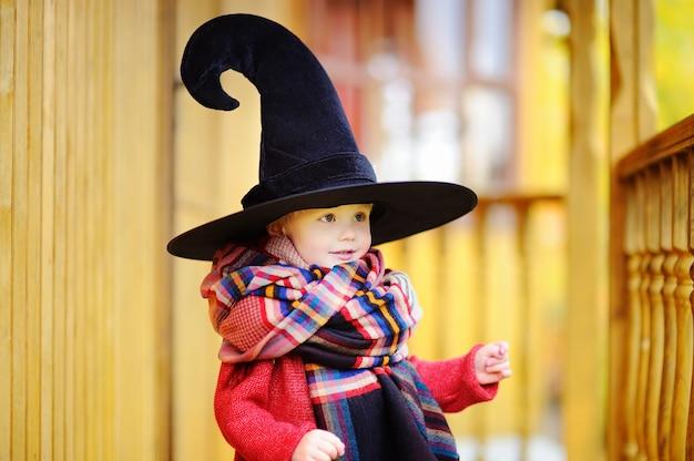 Enfant en bas âge au chapeau pointu jouant à l'extérieur. petit sorcier