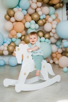 Enfant en bas âge bébé garçon garçon enfant en bas âge assis ride blanc petit cheval en bois jouet. zone photo de ballons.