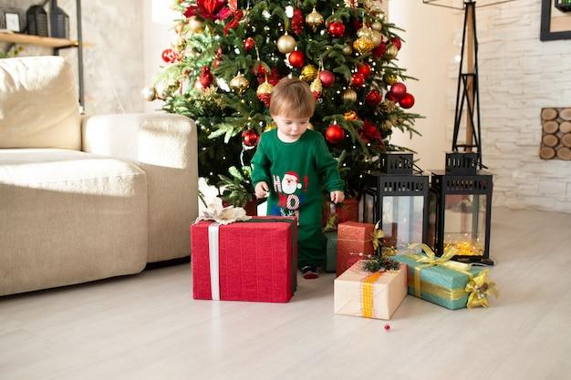 Enfant en bas âge avec cadeau de noël, arbre de noël